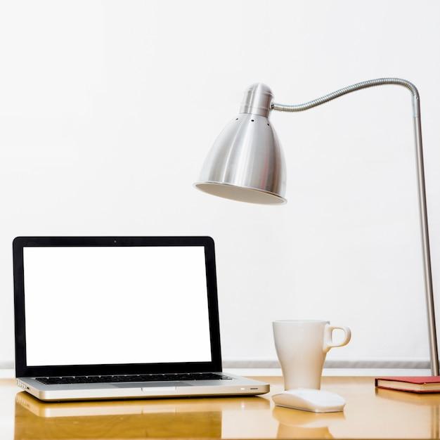 Ordinateur portable près d'une tasse, d'une lampe et d'une souris d'ordinateur Photo gratuit