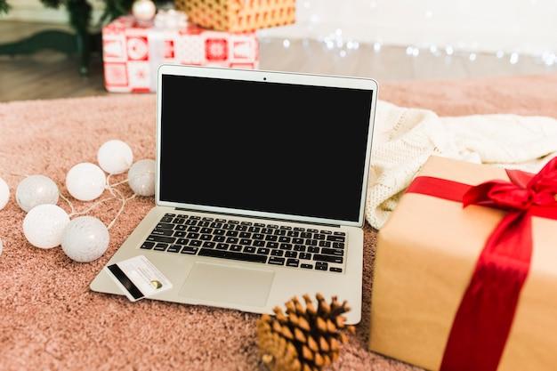Ordinateur portable à proximité d'une carte en plastique, de boîtes à cadeaux, d'un accroc en sapin et de guirlandes lumineuses Photo gratuit