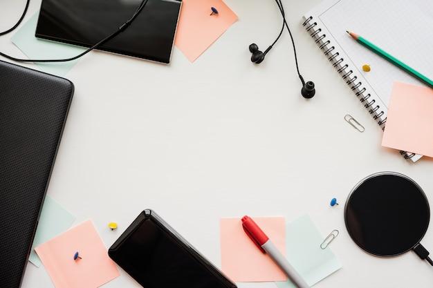 Ordinateur Portable, Smartphone, Banque D'alimentation, Chargement Sans Fil, écouteurs Et Articles De Papeterie Sur Un Bureau Blanc. Photo Premium