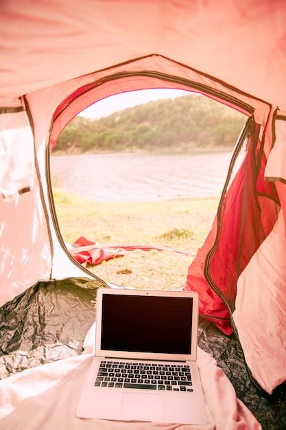 Ordinateur portable sous tente sur la plage Photo gratuit