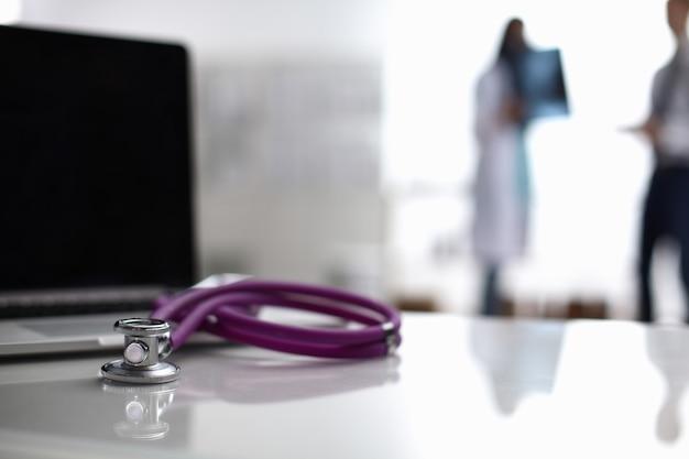 Ordinateur portable et stéthoscope sur le bureau, médecins en arrière-plan Photo Premium