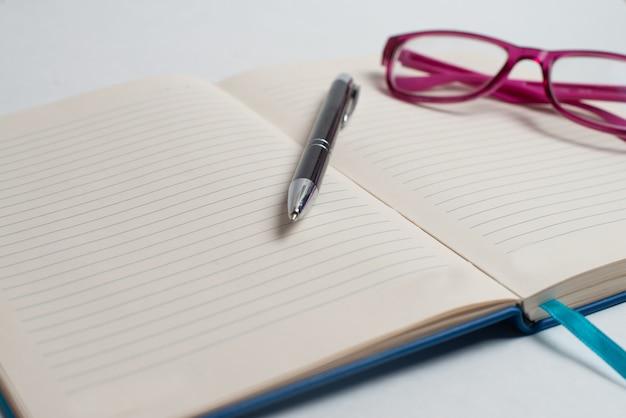 Ordinateur portable avec stylo noir et lunettes violettes sur le bureau Photo Premium
