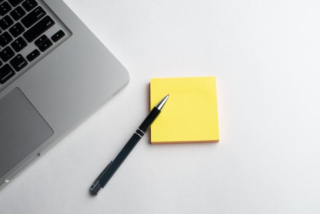 Ordinateur portable avec un stylo noir et un stick jaune Photo Premium