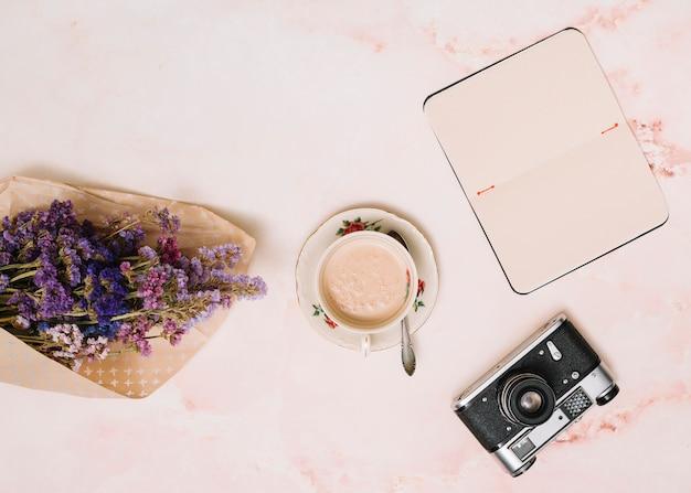 Ordinateur portable avec une tasse de café, une caméra et un bouquet de fleurs sur la table Photo gratuit