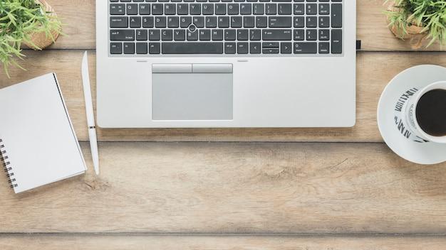 Ordinateur portable et tasse à café près de cahier sur la table Photo gratuit