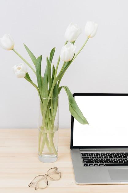 Ordinateur portable avec des tulipes blanches dans un vase sur la table Photo gratuit
