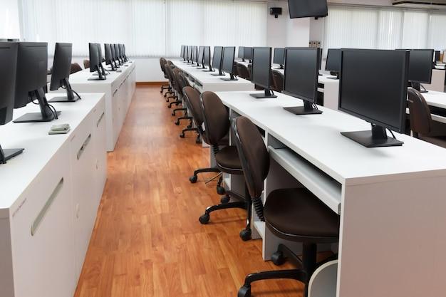 Ordinateurs de la classe. ne videz personne avec de nombreux ordinateurs moniteur sur un bureau blanc. Photo Premium