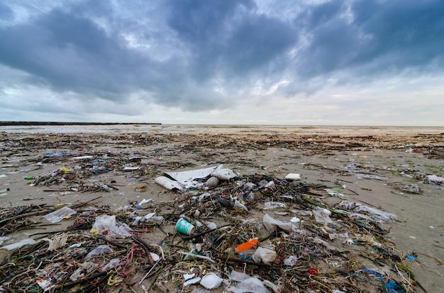 Ordures la bouteille en plastique de la mer de la plage se trouve sur la plage et pollue la mer Photo Premium