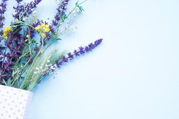 Oreille verte de blé et de fleurs dans la boîte à pois sur fond bleu Photo gratuit