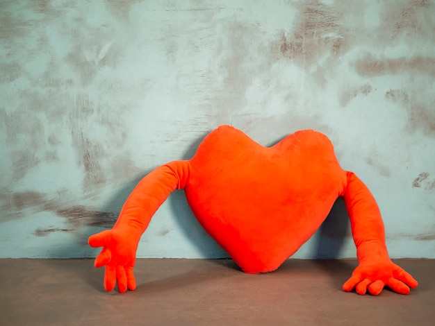 Oreiller en forme de coeur rouge saint valentin avec les mains sur le bleu Photo Premium
