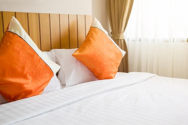 Oreiller orange et une couverture blanche sur le lit dans la ...