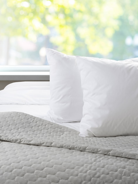 Oreillers blancs et drap sur un lit avec couvre-lit, Photo Premium