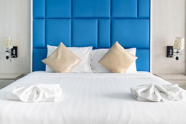 Oreillers de lit et couple dans une chambre moderne décorer avec ton couleur bleue Photo Premium