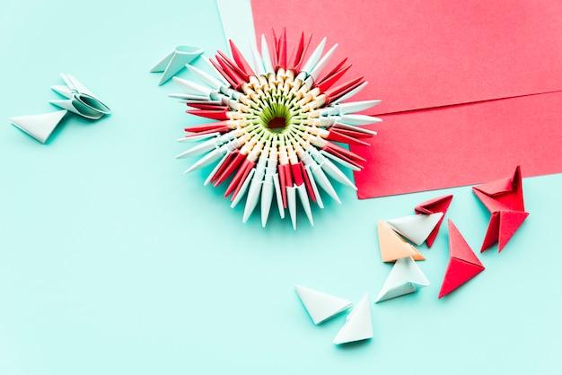 Origami de fleurs en papier à la main sur fond bleu sarcelle Photo gratuit