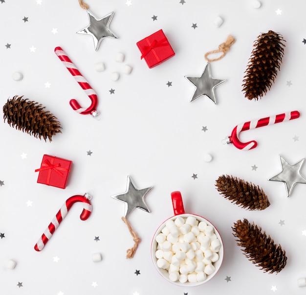Ornements, Pommes De Pin, Tasse De Chocolat Chaud Avec Des Boîtes De Cadeau De Guimauve Et Rouge Sur Fond Blanc Photo Premium
