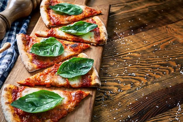 C; Ose Vue Sur Pizza Margarita En Tranches Sur Fond De Planche à Découper En Bois. Pizza Coupée Avec Espace De Copie Pour La Conception. Image Pour Le Menu, La Cuisine Italienne Photo Premium