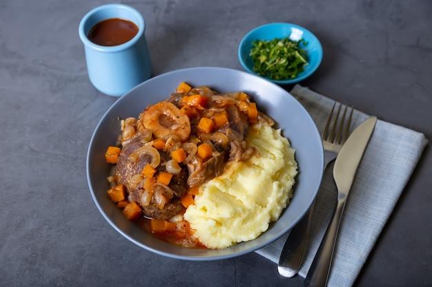 Osso Buco. Jarrets De Veau (boeuf) Avec Purée De Pommes De Terre, Gremolata Et Sauce. Plat Italien Traditionnel. Fermer. Photo Premium
