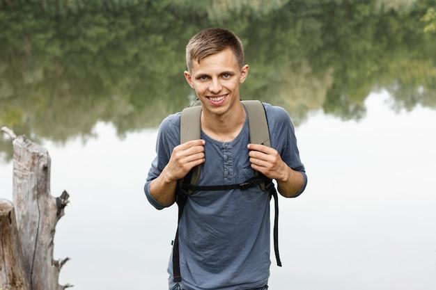 Oung garçon souriant à la caméra près d'un lac Photo gratuit