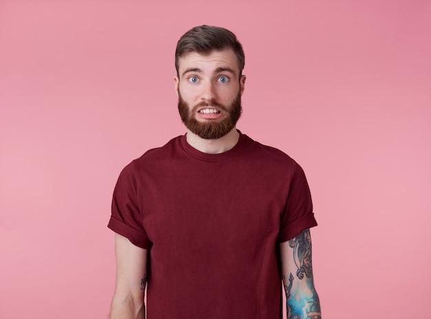 Oups! Quelque Chose Ne Va Pas! Portrait De Jeune Homme Barbu Tatoué Attrayant En T-shirt Blanc, A L'air Désolé Et Triste, Se Dresse Sur Fond Rose. Photo gratuit