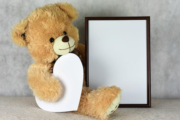 Un ours en peluche aimant garder un cadre avec un coeur le jour de la saint-valentin Photo Premium