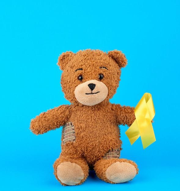 Ours en peluche brun est assis et tient dans sa patte un ruban de soie jaune sur un fond bleu Photo Premium