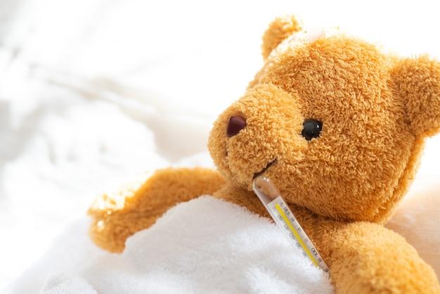 Ours en peluche couché malade au lit avec thermomètre et plâtre. Photo Premium
