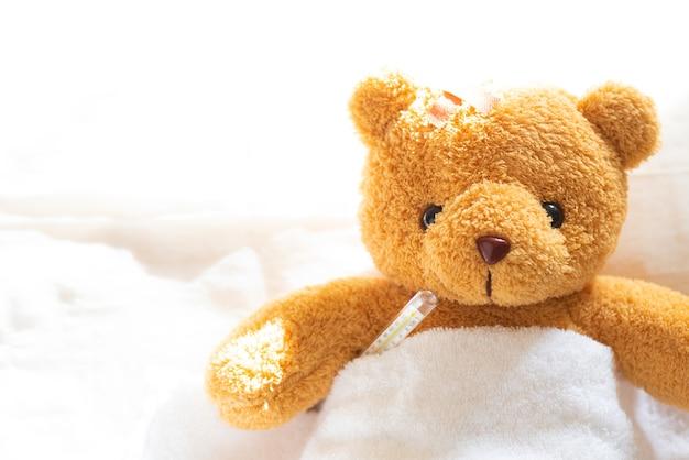 Ours en peluche lissant malade dans un lit d'hôpital avec un thermomètre et un plâtre. Photo Premium