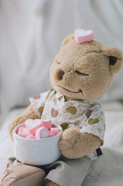 Ours en peluche marron tenant en forme de coeur rose guimauve Photo Premium