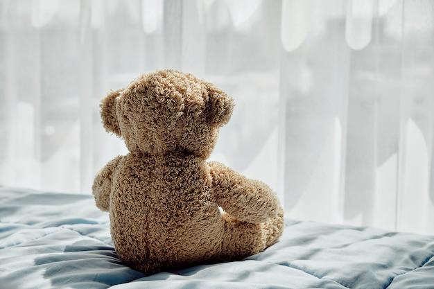 Ours poupée assis sur le lit Photo Premium