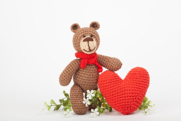 Ours tricoté avec un coeur. décor saint valentin. jouet tricoté, amigurumi, carte de voeux. Photo Premium
