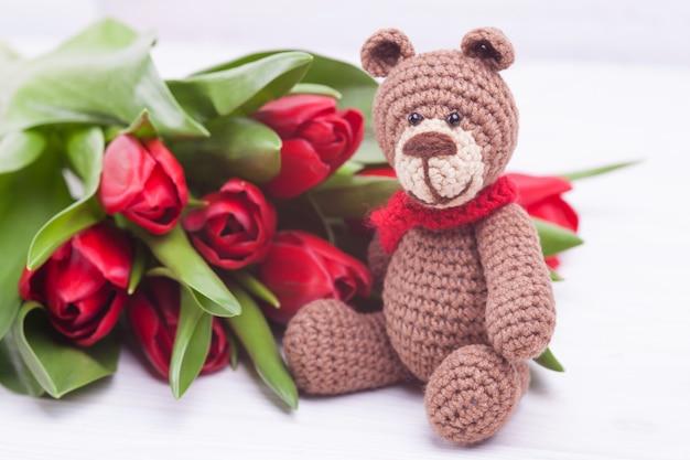 Ours tricoté. décor de fête. tulipes rouges délicates. la saint valentin. jouet tricoté à la main, amigurumi Photo Premium