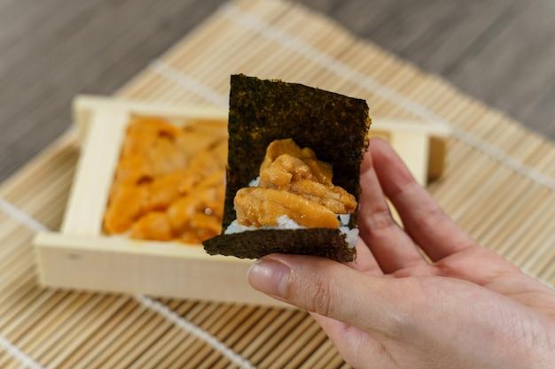 Oursin De Mer Uni Japonais Avec Du Riz Et Des Algues à La Main. Photo Premium