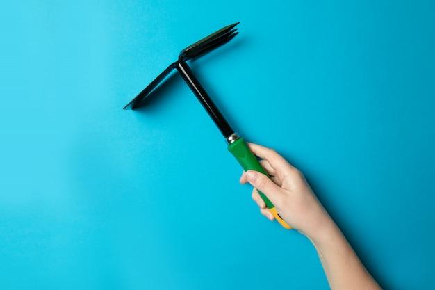 Outil de houe de jardin dans une main féminine pour le potager Photo Premium