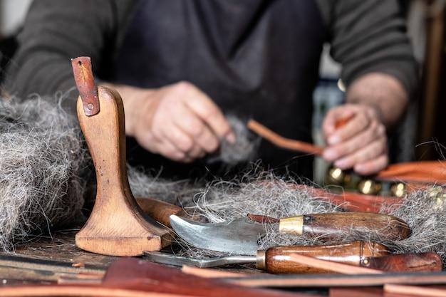 Outils d'artisan en cuir au premier plan avec l'homme travaillant derrière Photo Premium