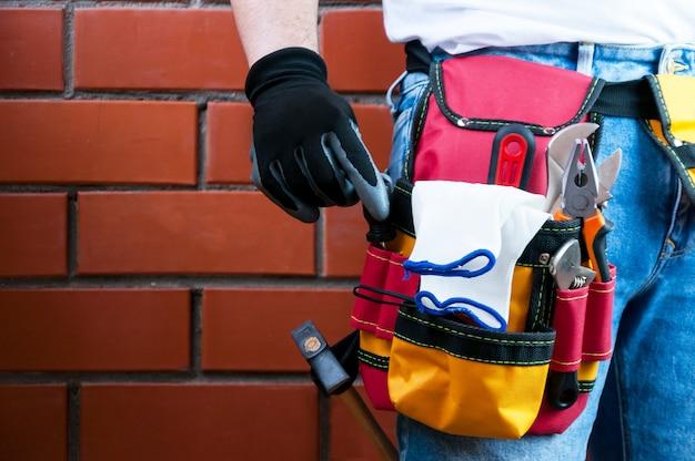 Des outils à la ceinture pour les outils. le constructeur tient un tournevis. Photo Premium
