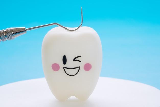 Outils dentaires et sourire dents modèle sur fond bleu. Photo Premium
