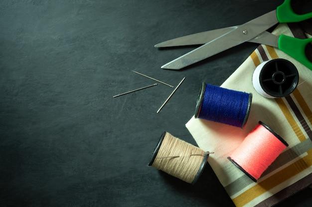 Outils et équipement de couture sur un sol en ciment noir. Photo Premium