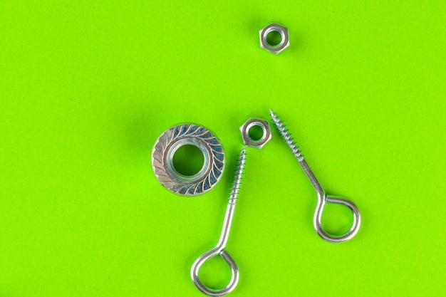 Outils d'ingénierie. boulons et écrous sur vert Photo Premium