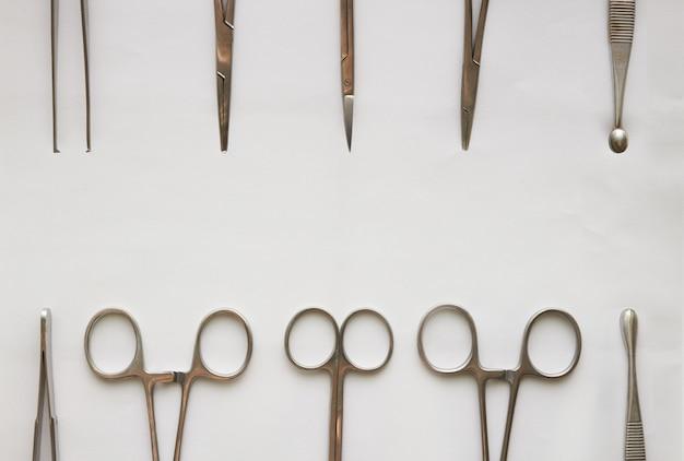 Outils de médecin, curetage, crampes, forceps et ciseaux sur blanc isolé Photo Premium