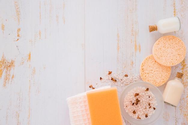 Outils de nettoyage de maison près de sel rose sur une table en bois Photo gratuit