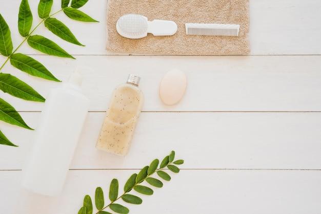 Outils de soins de la peau sur le bureau avec des feuilles vertes Photo gratuit