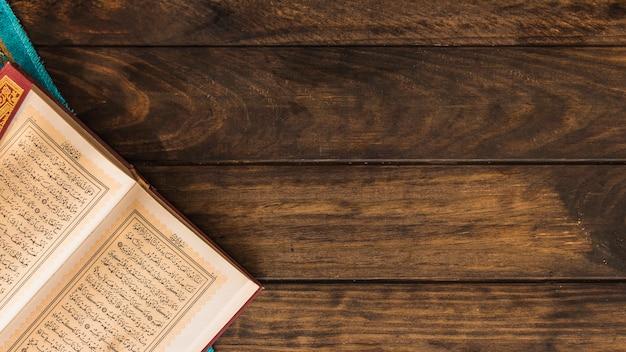 Ouvert coran et chiffon sur la table de bois Photo gratuit