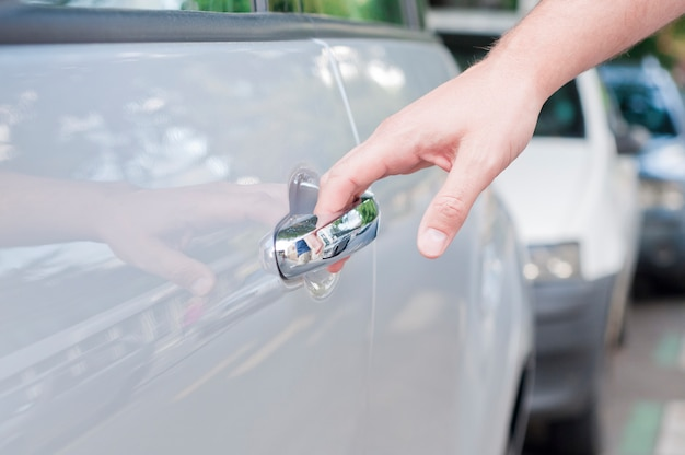 Ouverture de la porte de la voiture, man main ouvrant la porte de la voiture, de près Photo gratuit