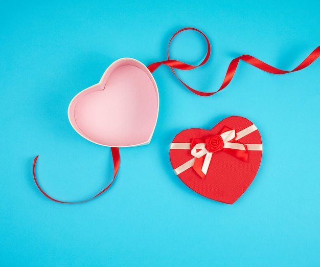 Ouvrez la boîte cadeau en forme de coeur rouge avec un arc sur un fond bleu Photo Premium