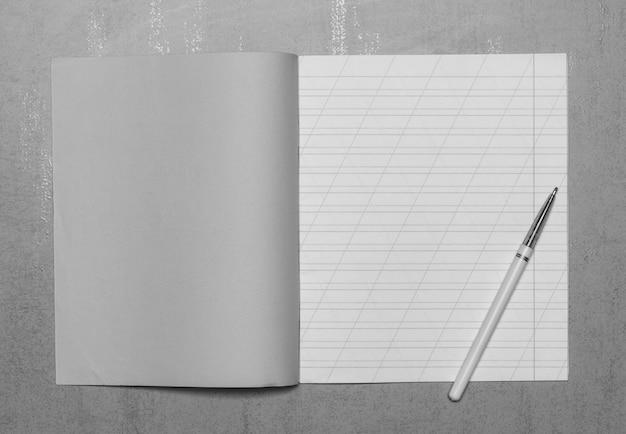Ouvrez le cahier d'écolier dans une ligne étroite avec une barre oblique pour apprendre l'orthographe, créez une copie avec espace copie et un stylo à bille sur fond gris, vue de dessus, photo en noir et blanc Photo Premium