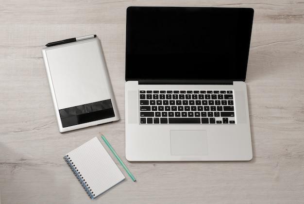 Ouvrez l'ordinateur portable, la tablette graphique et le bloc-notes au crayon sur une table lumineuse, vue de dessus Photo Premium