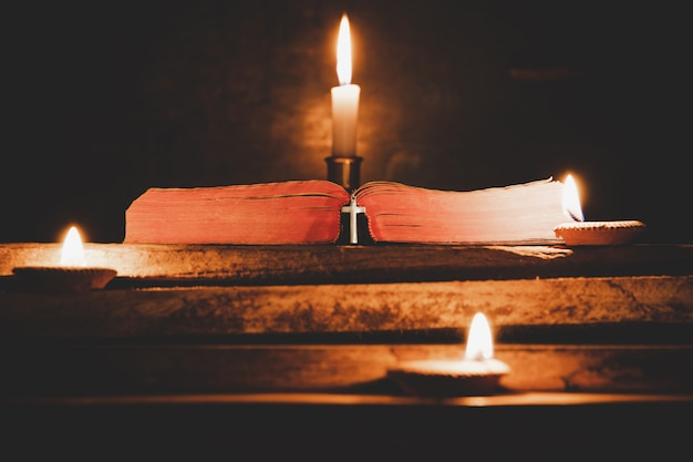Ouvrez la sainte bible et bougie sur une vieille table en bois de chêne. Photo gratuit