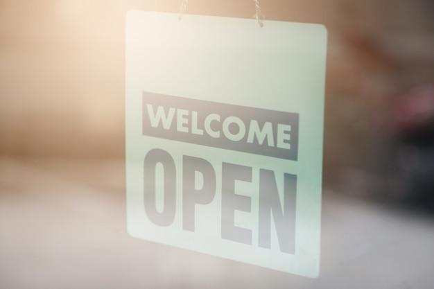 Ouvrez et signe de bienvenue large à travers le verre de la fenêtre pour faire savoir aux clients Photo Premium