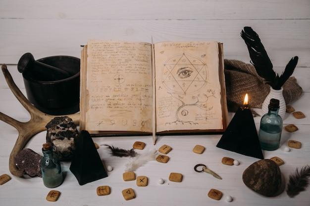 Ouvrez Le Vieux Livre Avec Des Sorts Magiques, Des Runes, Une Bougie Noire Et Des Herbes Sur La Table De La Sorcière. Photo Premium