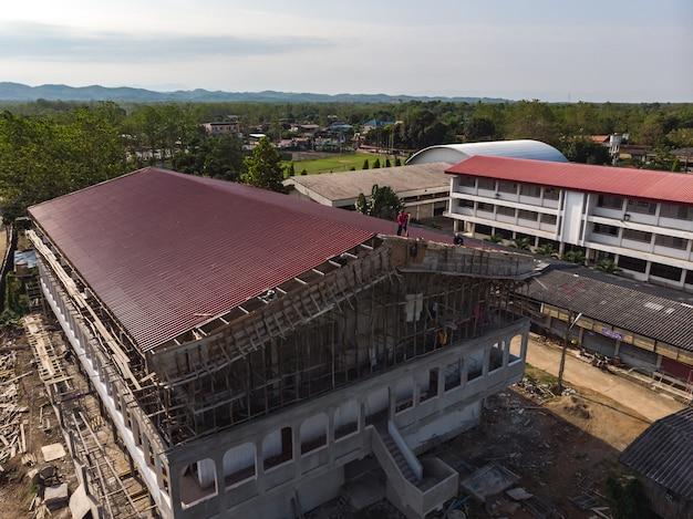 Ouvrier asiatique construisant le nouveau toit du stade Photo Premium